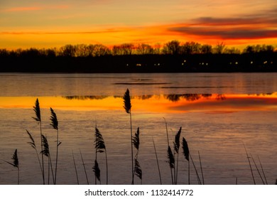 Sunset with reflection of trees and grass in the foreground with warm orange and red tones in the evening at swedish lake called Trummen, in Vaxjo, Smaland in Sweden - creating a dramatic sky