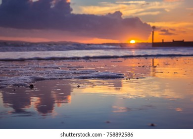 Sunset reflections on a sunny day on Bournemouth Beach, UK