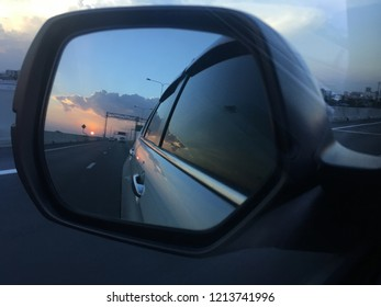 Sunset reflects shadow in a car mirrow.