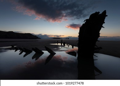 Sunset at Rhossili Bay and Worms Head showing remains of the ship The Helvetia, a Norwegian barque, which was wrecked during a storm in 1887 on the Gower peninsula, South Wales, UK