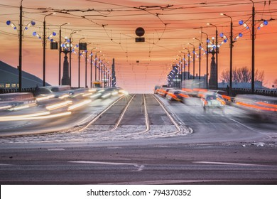 Sunset in Riga city with cars crossing the bridge creating light trails. Picturesque view on the highway with colorful sky.