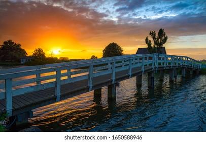Sunset river bridge in rural scene. Wooden bridge river sunset. Sunset river bridge view. Sunset rural river bridge