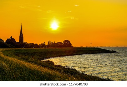 Sunset river shore silhouette landscape. River shore sunset silhouette panorama. Sunset river silhouette view. Sunset silhouette river scene