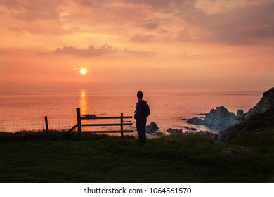 Sunset at Rockham Bay, Mortehoe, Woolacombe, Uk, with man looking out over the sunset