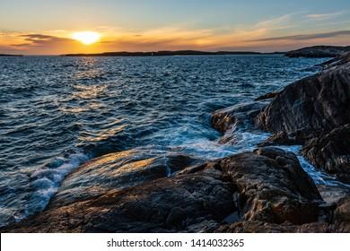 Sunset at a rocky beach with breaking waves. Swedish archipelago. Bohuslän