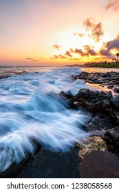 Sunset at a rocky beach with vivid warm colors and beautiful skies.