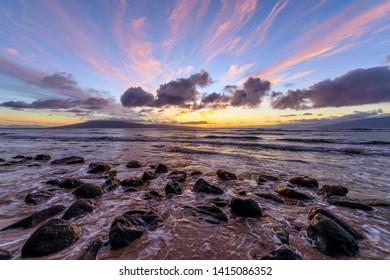 Sunset Rocky Coast - A colorful sunset view at a rocky shore of north-west coast of Maui island, with Lanai island at horizon. Maui, Hawaii, USA.