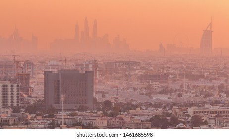 Sunset rooftop view on Dubai Marina with JLT skyline and Jumeirah beach in orange warm light. Houses and traffic on the road. Dubai, United Arab Emirates