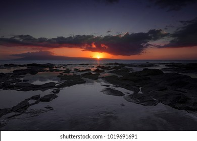 Sunset at rugged beach at hawaiian island