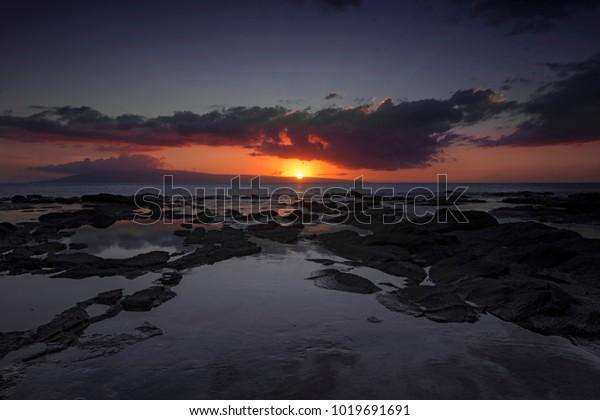 Sunset at rugged beach at hawaiian island