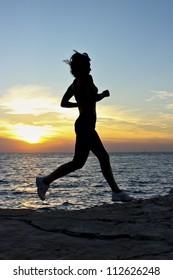 Sunset run Description: Woman running by the coast at sunset