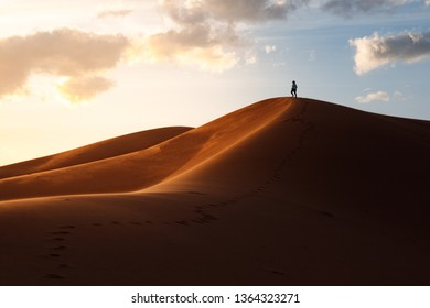 Sunset sahara desert, dunes in morocco merzouga, sand dunes, beautiful sunset people on a dune