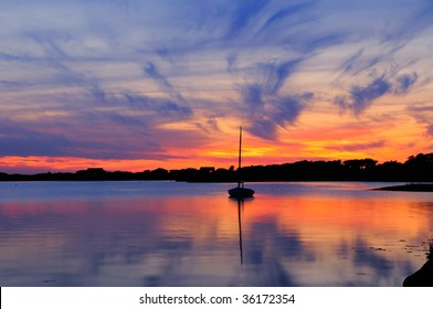 Sunset and sailboat in Martha's Vineyard, Massachusetts. Dramatic sky with vivid orange and blue cloudscape reflected on the water