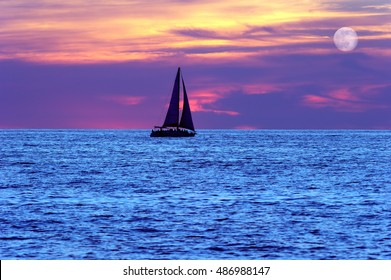 Sunset sailboat moon is a silhouette of a boat sailing along the water with full sails out as the moon rises in the evening sky.