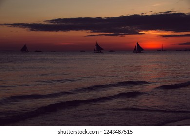Sunset with sailboats. Summer time. Travel to Philippines. Luxury tropical vacation. Boracay paradise island. Nature background. Seascape view. Tourism concept. Water transport