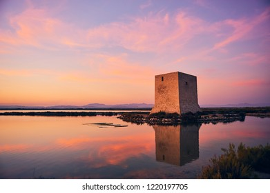 Sunset in the salt flats of Santa Pola, an autumn afternoon. Clear orange tones and cool shadows illustrate this typographic image of the Spanish Levante. Majestic the tower of the Tamarit.