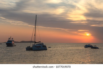 Sunset at Sant Antoni de Portmany, Ibiza, Spain. View from the beach near famous Cafe del Mar. The sun shines through the clouds. Silhouettes of yacht and boats, ripples on the Mediterranean Sea.