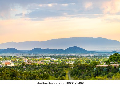 Sunset in Santa Fe, New Mexico skyline with golden hour light on green foliage summer plants and cityscape buildings with mountains silhouette