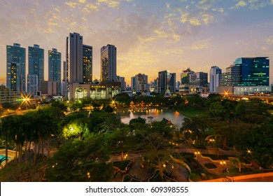 Sunset scence of modern office buildings and condominium in Bangkok city downtown with sunset sky and clouds at Bangkok , Thailand. Benjasiri Park