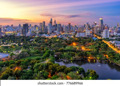Sunset scence of modern office buildings and condominium in Bangkok city downtown with sunset sky and clouds at Bangkok , Thailand. Lumpini park