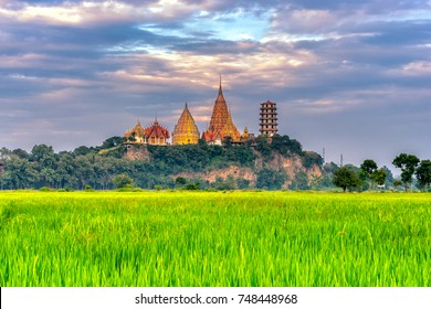 Sunset scence of Wat Tham Sua Temple with rice fields in Kanchanaburi Province, Thailand.