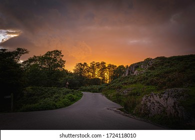 Sunset scene with atmospheric mood in English Lake District.Country road in scenic valley lit by evening light reflected from clouds and sun setting behind bunch of trees with dramatic sky above.