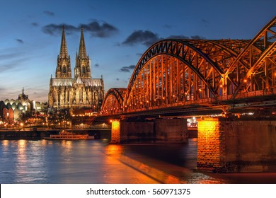 Sunset scene in Cologne (Koln) in North Rhine Westphalia region of Germany, surprising the Cologne Cathedral (Kolner Dom) and the Hohenzaller Bridge over the Rhine River.