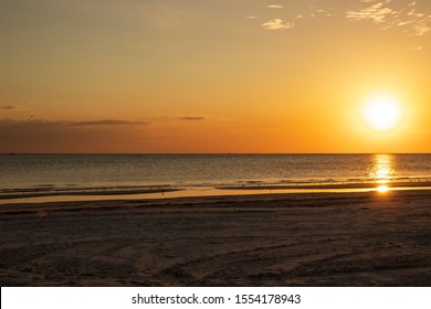 Sunset scene at Fort Myers Beach, FL, with bright orange color, sandpiper silhouette and reflection, seagulls & sailboat silhouette