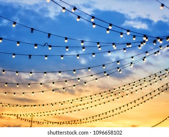 Sunset scene of light bulbs on string wire