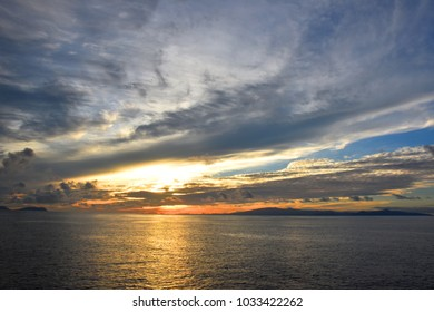 Sunset scene in the middle of the sea, with golden Sun ray and cloudy sky