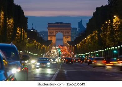 sunset scene in Paris city. Long exposure photo of street traffic near Arc de Triomphe, Champs Elysees boulevard.