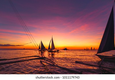 Sunset in the sea behind silhouette of sailboat at Boracay Island, Philippines.