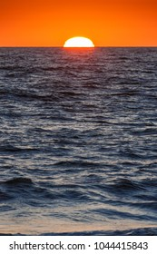 Sunset at sea. Cadiz coast in Andalucia (Spain). Amazing orange sky when the sun touch the horizont