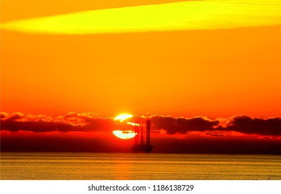 Sunset sea oil rig silhouette panorama. Oil rig sunset silhouette. Oil rig platform sunset sea view. Sunset oil rig platform silhouette scene