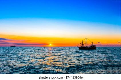 Sunset sea ship silhouette view