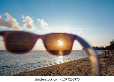 Sunset at the sea through sunglasses on the tropical island