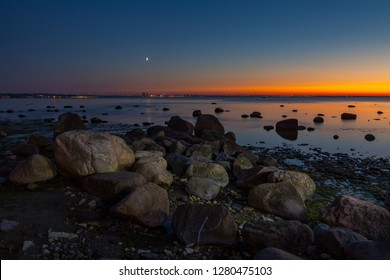 Sunset seascape with boulders on the shore of Baltic sea. Amazingly colorful sky.