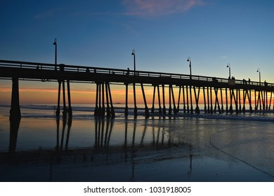 Sunset seascape with panoramic view of the Imperial Beach Pier and the people silhouettes, in San Diego Southern California.
