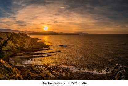 A sunset in the seaside with rocks and reflections