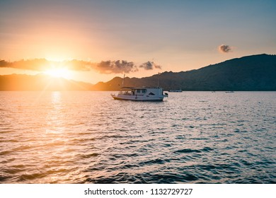 Sunset seen from the ocean with a boat
