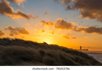 Sunset seen from the sand dunes of Ostend at sunset with the skyline of the city in the background, Belgium.