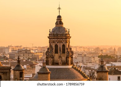 Sunset Seville - A close-up golden sunset view of the dome and bell tower at the top of the 16th-century Renaissance style Iglesia de la Anunciación - The Annunciation Church in Seville, Spain.
