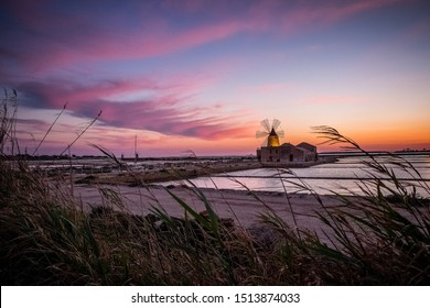 Sunset .Shallow salt pools and windmills Trapani Sicily .The salt from these marshes is considered Italy's finest and has been big business for centuries; today, only a cottage industry remains