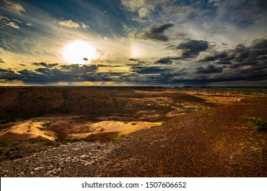 Sunset shining spotlight over resilient tree in sand dune in shadowy ravine with clouds pouring rain in the distance over village and hills in sahel outside Niamey capital of Niger during rainy season