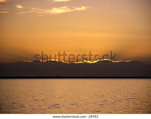 Sunset shining though clouds, horizontal light ray.