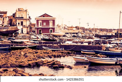 Sunset in Sicily, Acitrezza harbor with fisher boats next to Cyclops islands, Catania