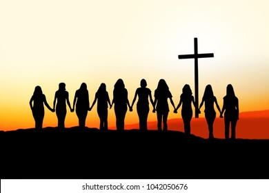 Sunset silhouette of 10 young women walking hand in hand toward a Christian Cross.