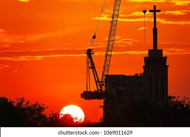 Sunset silhouette construction building tower crane cross.