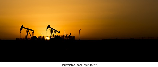 Sunset and silhouette of crude oil pump in oilfield- wide panorama view.