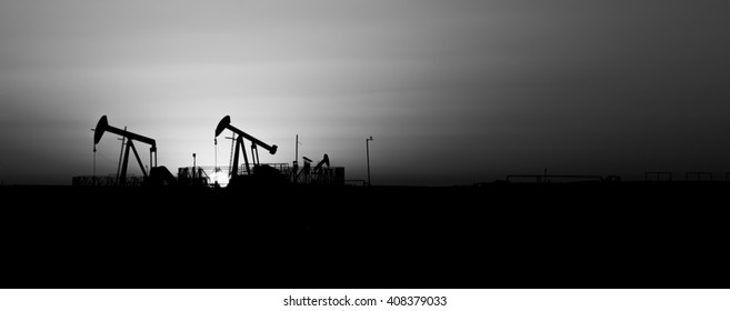 Sunset and silhouette of crude oil pumping units - wide panorama view - oilfield- Black and white.